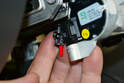 To replace the electrical portion of the switch, begin by disconnecting the switch harness (red arrow).
