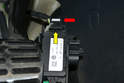 Turn the pedal over and squeeze the clip on the top of the wiring connection (red arrow) and separate the connection from the pedal by pushing it up (yellow arrow).