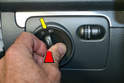 Headlight Switch - Press the switch straight in towards the front of the car (red arrow) and turn the switch clockwise until half way between the off and on position (yellow arrow).