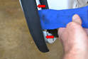 Begin by opening the door and using your trim tool to remove the plastic weather stripping along the inside section of the door (red arrows).