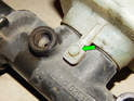 Use a pair of needle-nose pliers to pull the retaining pin (green arrow) up and out of the master cylinder.