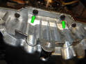 Loosen and remove the two 5mm hex bolts (green arrows) along the back edge of the oil pan.