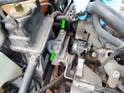 Once the engine is secured on a floor jack, loosen and remove the two 16mm bolts (green arrows) securing the engine mount to the engine.