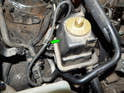 Pull the cable holder off the threaded nut (green arrow) next to the power steering fluid reservoir.