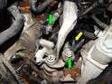 Begin by pulling the snap clips off the gearshift cable ends (green arrows).