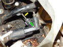 Pull up on the retaining clip (green arrow) with a small pick and pull the hydraulic line fitting (yellow arrow) out of the slave cylinder.