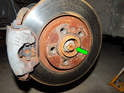 Left and Right Sides - The first step is to loosen, but do not remove the 30mm 12 point nut (green arrow) securing the axle to the wheel hub.