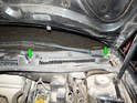 Use a flathead screwdriver to carefully pry the plastic caps off the tops of the wiper arms (green arrows).