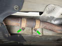 Loosen and remove the two 16mm nuts (green arrows) holding the clamp in place over the two sections of exhaust.