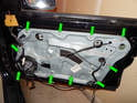 Loosen and remove the ten 10mm bolts (green arrows) holding the carrier panel to the door frame.