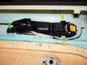 From inside the door panel, loosen and remove the Phillips head screw (green arrow).