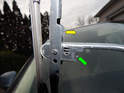 Lift each wiper arm up off the windshield and turn it over to access the release tab (green arrow).