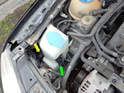 Begin by pulling the wiper fluid pump (green arrow) up and out of the reservoir.