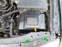 Loosen and remove the two Phillips head screws (green arrows) and lift the access panel (yellow arrow) up and out of the engine compartment.