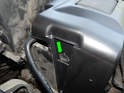 Shown here is one of the release tabs for the battery cover (green arrow).