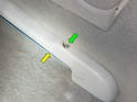 Once the plug is removed, loosen and remove the Phillips head screw (green arrow) and pull the seat rail cover (yellow arrow) off.