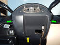 Loosen and remove the two Phillips head screws (green arrows) underneath the steering column.