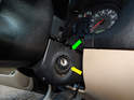 You'll want to pull the lower cover slightly outward (green arrow) over the ignition switch (yellow arrow).