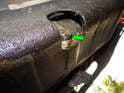The oil drain bolt (green arrow) is located on the bottom edge of the oil pan near the rear.