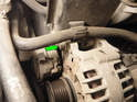 Loosen and remove the top 13mm bolt (green arrow) holding the alternator in place.