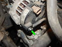 Loosen and remove the 13mm nut (green arrow) holding the positive lead to the alternator.