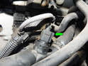 Shown here is the ECU coolant temp sender mounted in the upper radiator hose assembly (green arrow) .