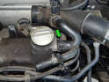 Loosen and slide back the hose clamp (green arrow) holding the vacuum hose to the oil filler on the valve cover.