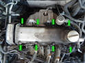 Loosen and remove the eight 10mm nuts (green arrows) holding the valve cover to the cylinder head.