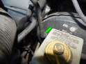 Use a flathead screwdriver to carefully pull the fitting (green arrow) out of the brake booster.