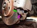 Note the tab (green arrow) molded into the caliper.