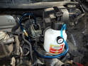 Remove the protective cap from the brake fluid reservoir and attach the connection for the pressure bleeder.