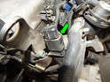 Press the tab on the backside of the electrical connector (green arrow) to the camshaft position sensor and pull it off.