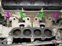 From above the manifold, loosen and remove the two 6mm Allen head bolts (green arrows) and the two 13mm nuts (purple arrows) securing the manifold to the cylinder head.