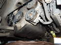 Begin by removing the serpentine belt from the engine pulleys.
