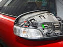 Press the tab (green arrow) in carefully and lift the turn signal lens out of the mirror housing.