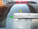 Begin by prying up the cover at the end of the rear wiper arm (green arrow).