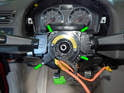 Remove the four small Phillips head screws holding the clockspring to the steering column (green arrows).