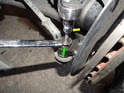 Left and Right Sides: Begin by loosening the 15mm nut (green arrow) that secures the tie rod ball joint to the front wheel carrier.