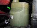 Take note of the minimum and maximum fluid level marks molded into the pump reservoir (green arrow).