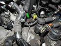 Press the tab on the electrical connector (green arrow) going to the crankshaft sensor and pull it off.