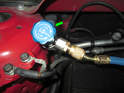 If you are using a set of AC manifold gauges, connect the low (green arrow) and high side pressure hoses to each port.