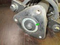Left and right sides of car - Use a flathead screwdriver to pop the protective cap (green arrow) off the top of the strut mount.