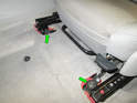Remove the two 13mm bolts (green arrows) holding the front section of the seat rails to the frame.