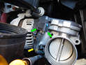 Press the tabs (green arrows) on either side of the electrical connection and pull it off the clip (yellow arrow) on the throttle body.