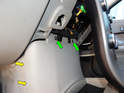 Loosen and remove the two T25 Torx screws (green arrows) holding the front of the center console in place.