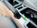 Locate the access panel right next to the emergency brake (green arrow).