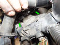 You can just barely see the two 13mm nuts (green arrows) in this photo after lifting up the radiator hose.