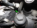 Use a pair of dykes to cut the crimped end off the hose clamp (green arrow) holding the breather hose to the oil filter housing.