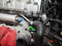 Loosen and remove the 10mm bolt (green arrow) holding the fuel supply line to the cylinder head.