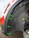 Remove the five T25 Torx screws (green arrows) and the 10mm plastic nut (Yellow arrow) securing the front of the wheel liner to the car.